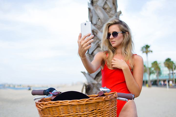 Woman in sexy bikini making self portrait with a cell phone camera while sitting on classic bicycle at summer vacation,charming female in fashion sunglasses taking a picture of herself on smart phone.