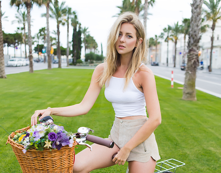 Full length portrait of a gorgeous female dressed in trendy clothes standing outdoors with her retro bicycle and looks at you, attractive blonde hair woman posing for the camera with vintage bike.