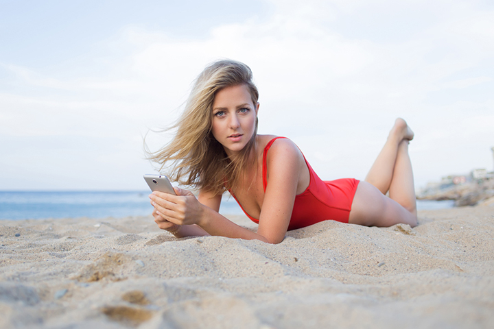 Portrait of a gorgeous blonde hair woman dressed in red swimsuit using cell phone while relaxing on the beach, beautiful female looking photos on a smart phone during summer vacation holidays at sea.