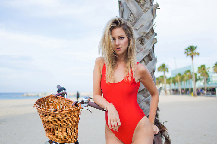 Half length portrait of young sexy woman dressed in trendy swimsuit standing on the beach with her vintage bike, attractive female in swimwear enjoying rest in summer holidays strolling with bicycle.